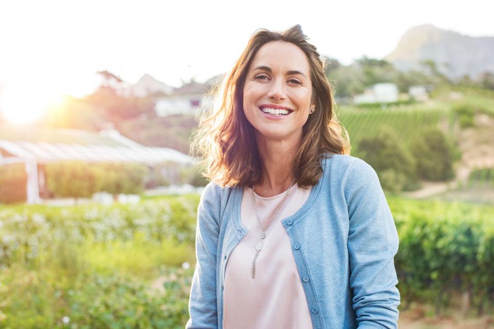 woman outside in field smiling