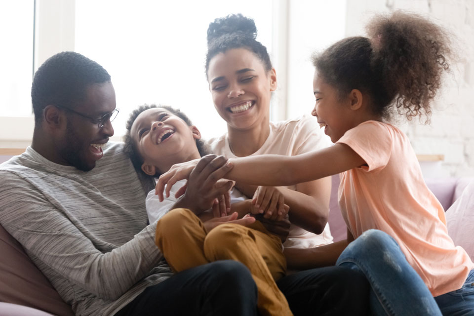 happy family laughing on the couch